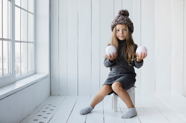 Niña rubia que ofrece bolas de nieve