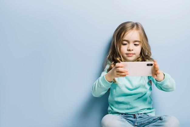 Niña rubia que se sienta contra fondo azul que mira el vídeo en el teléfono móvil