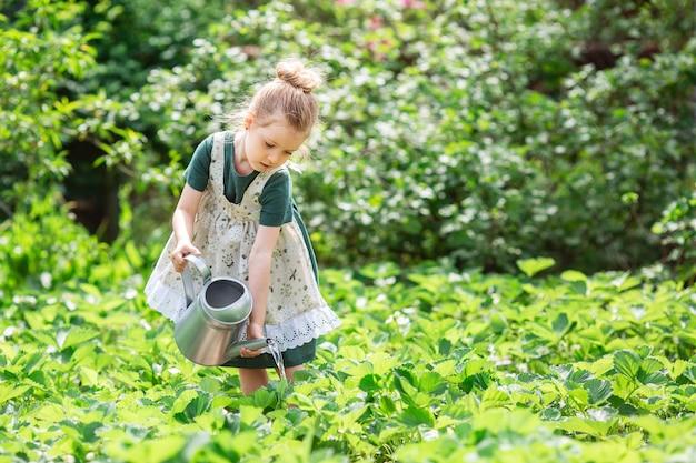 Niña rubia con una regadera en el jardín.