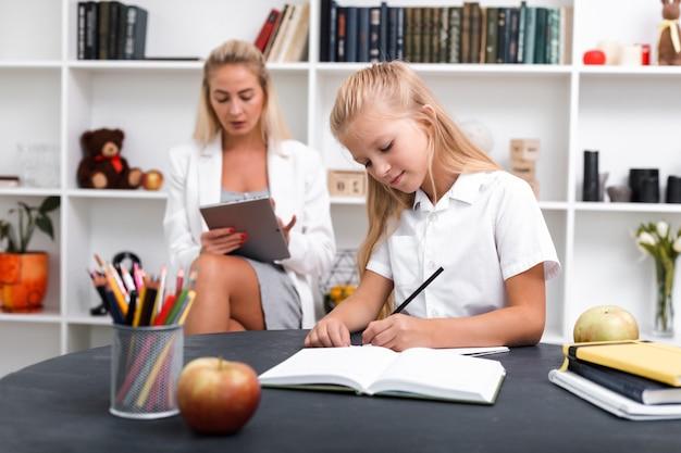 Niña rubia sentada en el escritorio haciendo la tarea mientras la madre está trabajando en tableta