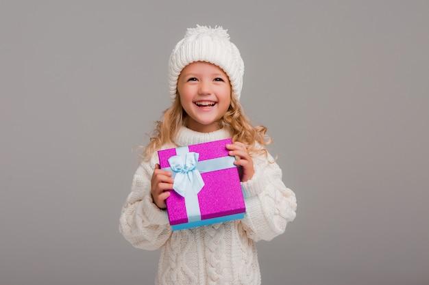 Niña rubia con sombrero de invierno sonriendo sosteniendo una caja de regalo