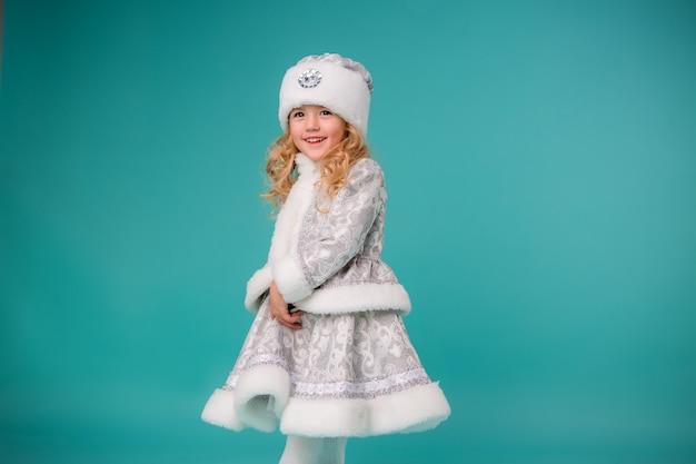 Niña rubia sonriendo en traje de doncella de nieve aislar en la pared azul