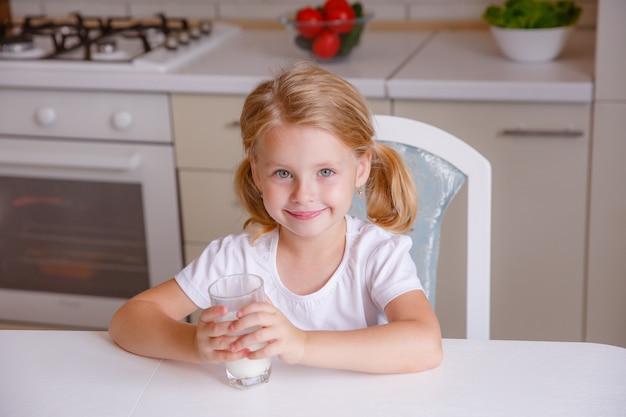 Niña rubia sonriente bebiendo leche en la cocina