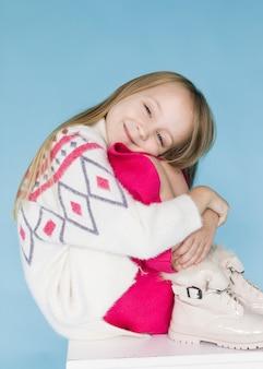 Niña rubia sonriente posando moda