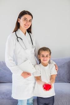 Niña rubia sosteniendo corazón con doctora