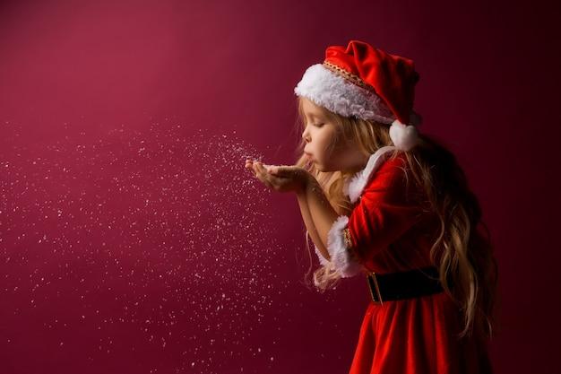 Niña rubia en un traje de santa sopla nieve de sus manos