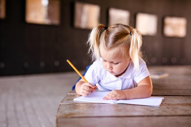 Niña rubia en uniforme escolar estudiando en el parque