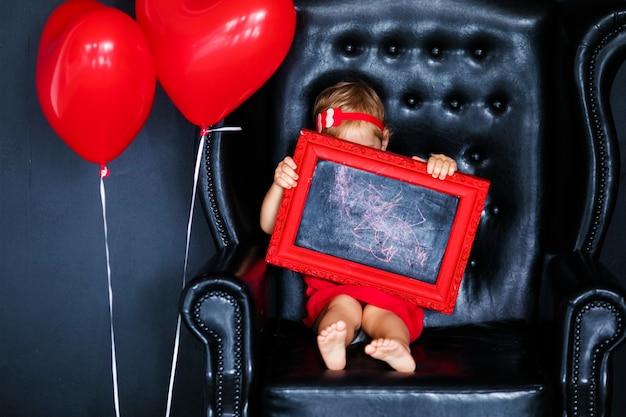 Niña rubia en vestido rojo con corona roja con corazones sentado en el sillón con globo de corazón rojo en el día de san valentín.