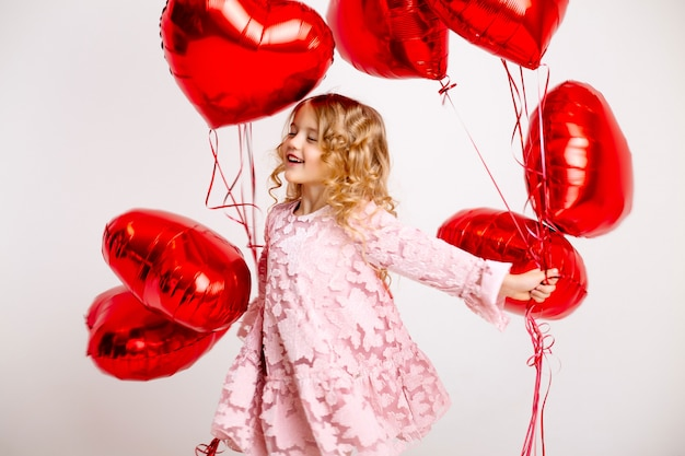 Niña rubia con un vestido rosa está sonriendo y sosteniendo un montón de globos rojos en forma de corazón concepto de día de san valentín