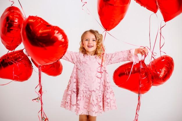 Niña rubia con un vestido rosa está sonriendo y sosteniendo un montón de globos rojos en forma de corazón en una pared blanca concepto de día de san valentín