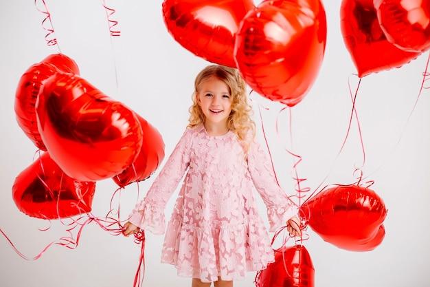 Niña rubia con un vestido rosa está sonriendo y sosteniendo un montón de globos rojos en forma de corazón en una pared blanca