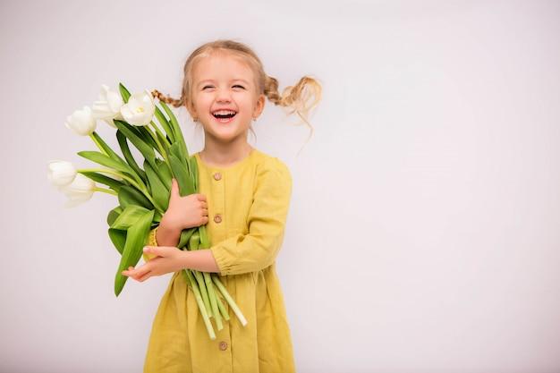 Niña rubia en vestido verde con tulipanes sobre fondo blanco.