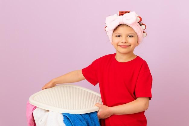 Una niña con rulos va a lavar cosas sucias. lavandería y tintorería.