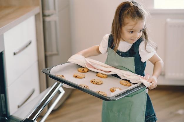 Niña saca una bandeja de galletas del horno