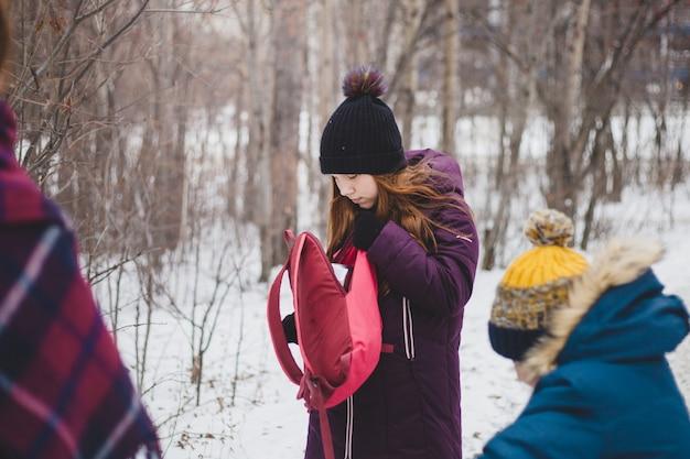 Una niña saca cosas de una mochila en un paseo de invierno con su familia en el bosque o parque
