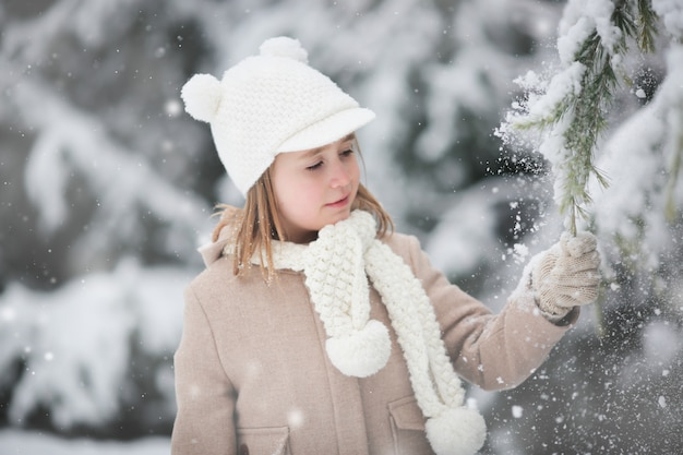 La niña sacude la nieve de un abeto sobre sí misma.