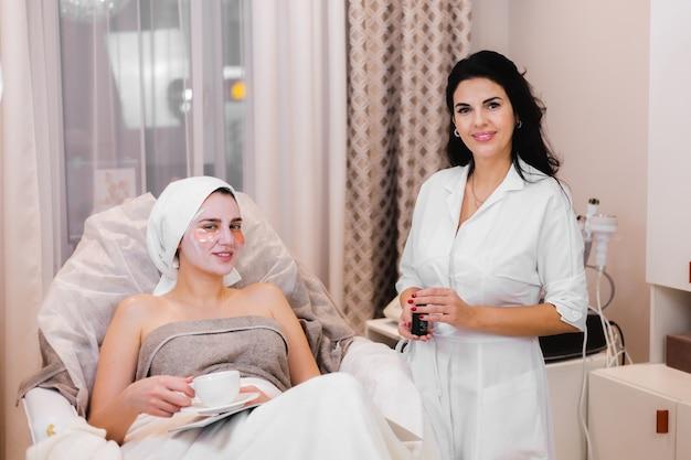 Una niña en un salón de belleza en una oficina de cosmetología se encuentra en la cama se relaja con una máscara