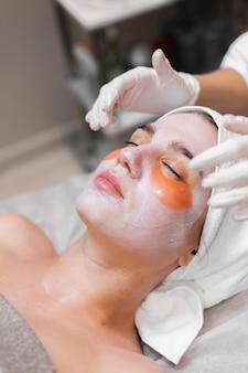 Una niña en un salón de belleza en una sala de cosmetología yace en una cama se relaja con una máscara en la cara y parches debajo de los ojos