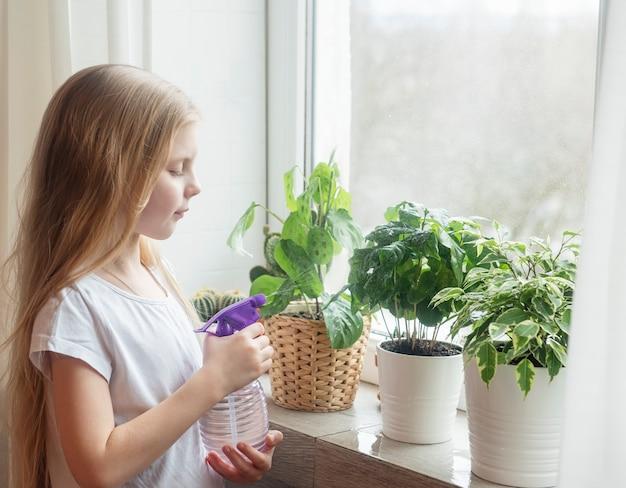 Niña salpicando agua sobre las plantas de la casa