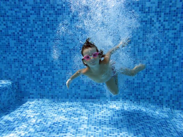 Niña salta y nada en la piscina bajo el agua