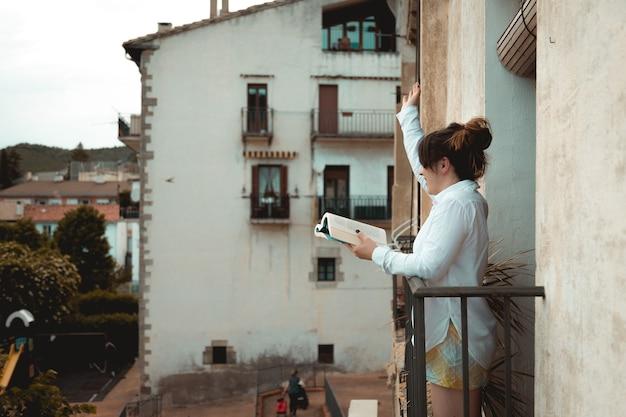 Niña saluda desde su balcón mientras sostiene un libro