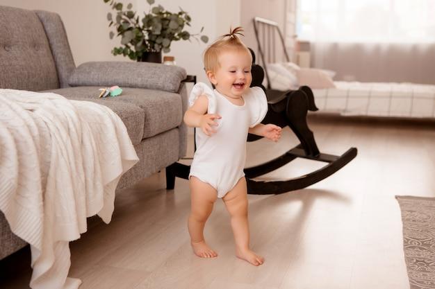 Niña sana en una habitación junto a un sofá gris está aprendiendo a caminar