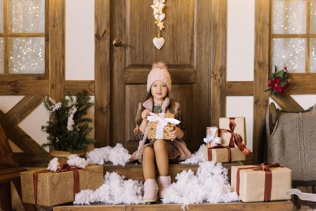 Una niña de seis años se sienta en el porche de una casa de invierno en un estudio fotográfico y sostiene un regalo de navidad