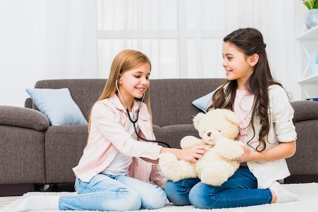 Niña sentada en la alfombra jugando con un peluche usando un estetoscopio en la sala de estar