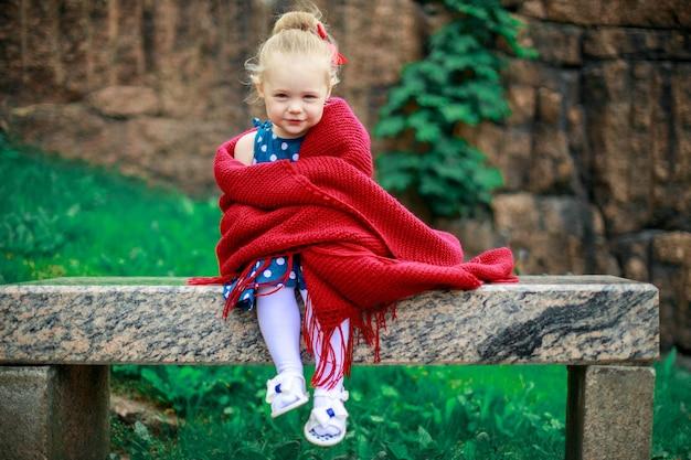 Una niña está sentada en un banco envuelta en una manta de lana.