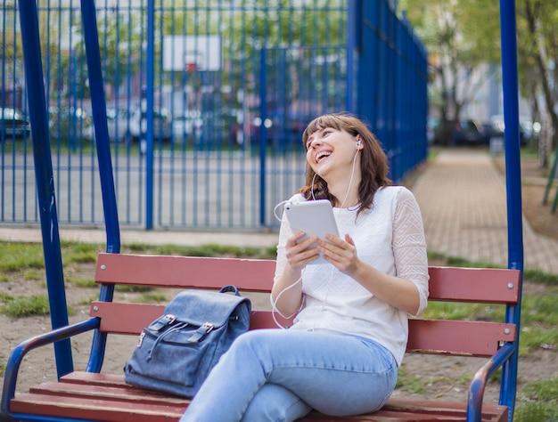 La niña está sentada en un banco con una tableta y riendo, mirando hacia arriba. chica morena con una chaqueta blanca y jeans en la calle