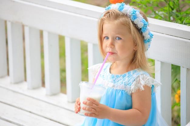 Niña sentada en un banco con un vestido azul y bebe un batido