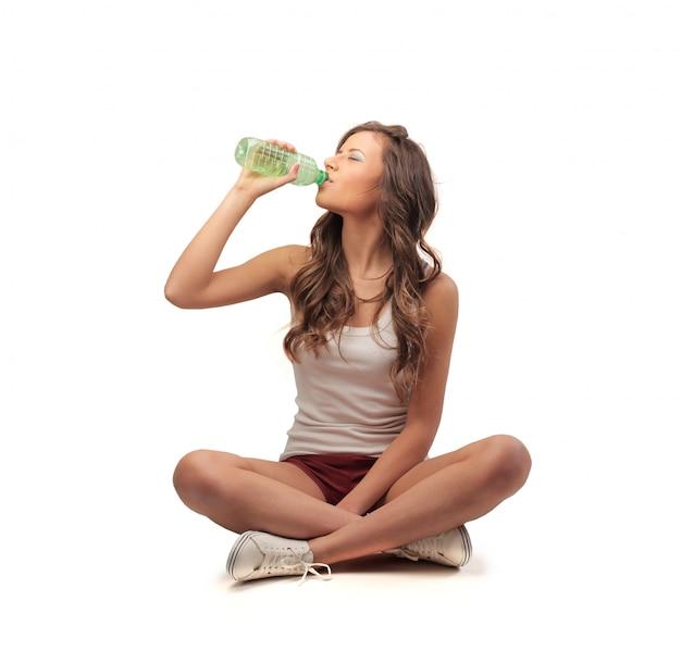 Niña sentada y bebiendo de una botella
