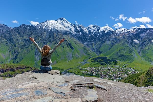 Niña sentada en el borde del acantilado y mira las cimas de las montañas cerca de la aldea de gergeti en georgia, bajo el monte kazbegi. chica mira las cimas de las montañas