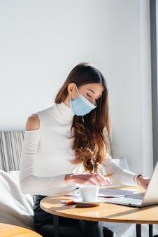 Una niña está sentada en un café con una máscara y trabajando en una computadora