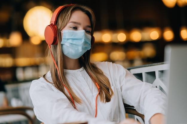 Una niña sentada en una cafetería con auriculares brote de coronavirus
