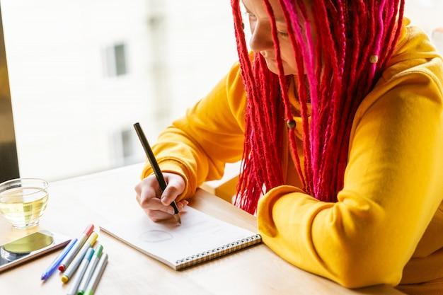 Niña sentada en la cafetería y dibuja con lápices de colores y marcadores en el cuaderno.