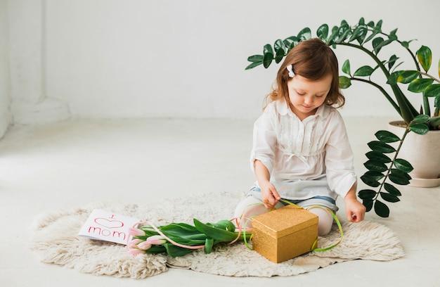 Niña sentada con caja de regalo y tarjeta de felicitación