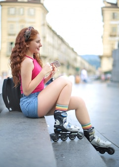 Niña sentada en la calle, usando patines
