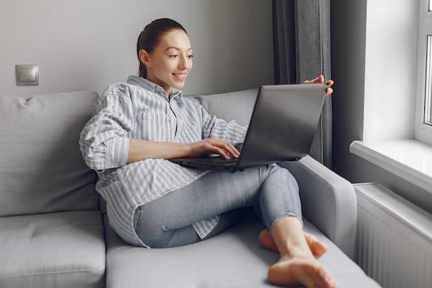Niña sentada en casa y usar la computadora portátil