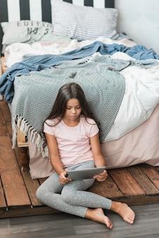 Niña sentada cerca de la cama mirando tableta digital