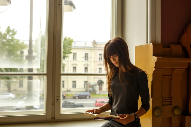 Niña sentada cerca de la ventana leyendo un libro