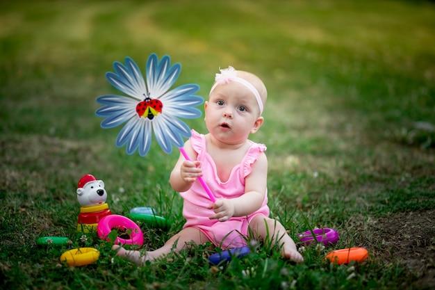 Niña sentada en el césped en el verano y jugando con un tocadiscos
