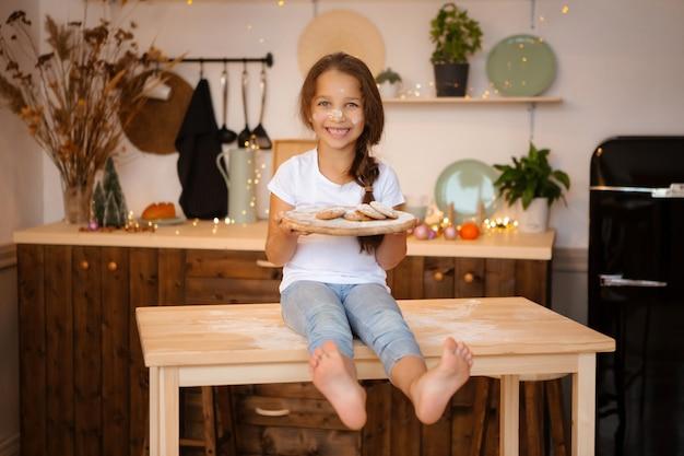 Niña sentada en la cocina de navidad en la mesa