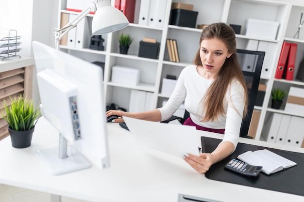 Una niña sentada en una computadora de escritorio y trabajar con documentos.