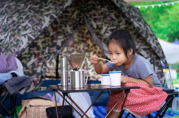 Niña sentada y desayunando frente a la tienda mientras acampa