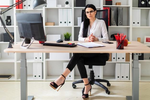 Una niña sentada en el escritorio de la computadora. al lado de la niña se encuentran documentos y un marcador.