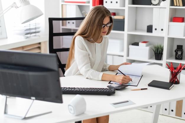 Una niña sentada en el escritorio de la computadora en la oficina, sosteniendo un lápiz en la mano y tomando notas