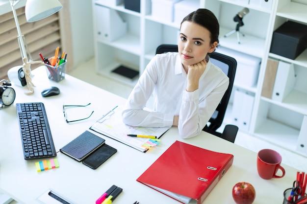 Una niña está sentada en el escritorio de la computadora en la oficina.