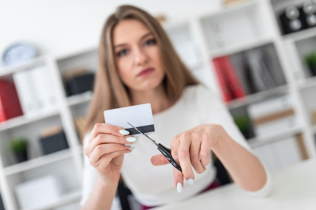 Una niña sentada en un escritorio en la oficina y corta una tarjeta bancaria con unas tijeras.