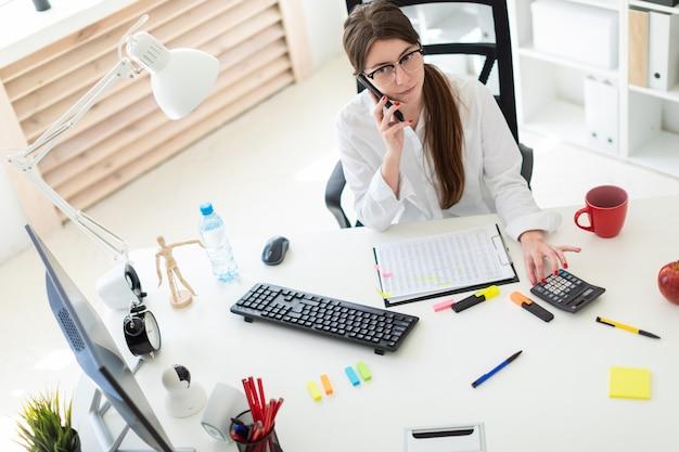 Una niña sentada en el escritorio de la oficina, hablando por teléfono y contando con la calculadora.